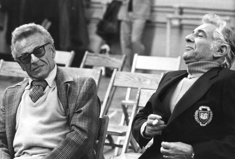 Alan Jay Lerner and Leonard Bernstein sit and talk during a rehearsal.
