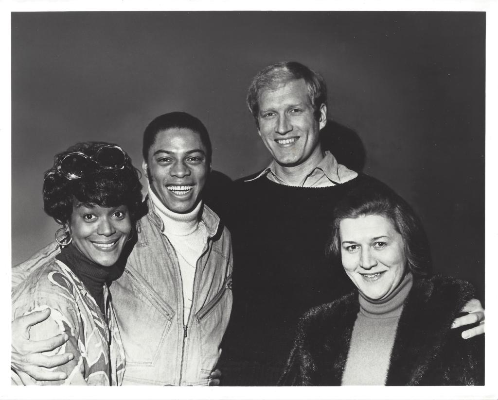 Emily Yance, Gilbert Price, Ken Howard, and Patricia Routledge pose for a photograph with their arms around each other.