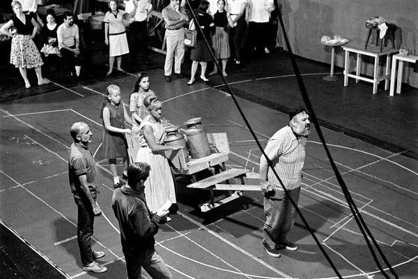 Zero Mostel pulls a cart on a rehearsal stage marked with lines.  Jerome Robbins stands observing him and the rest of the cast.