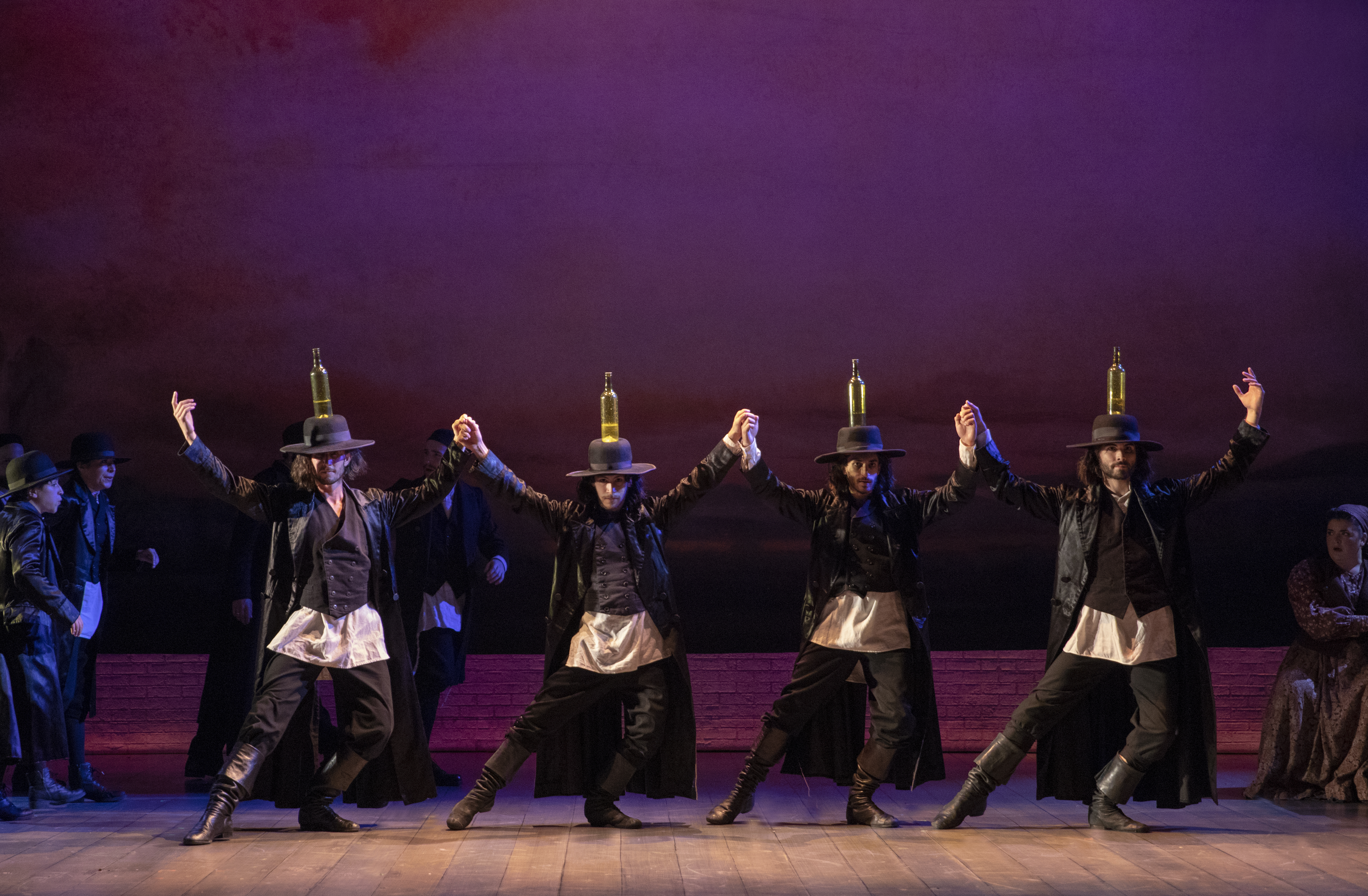 Male dancers hold hands and balance bottles on the